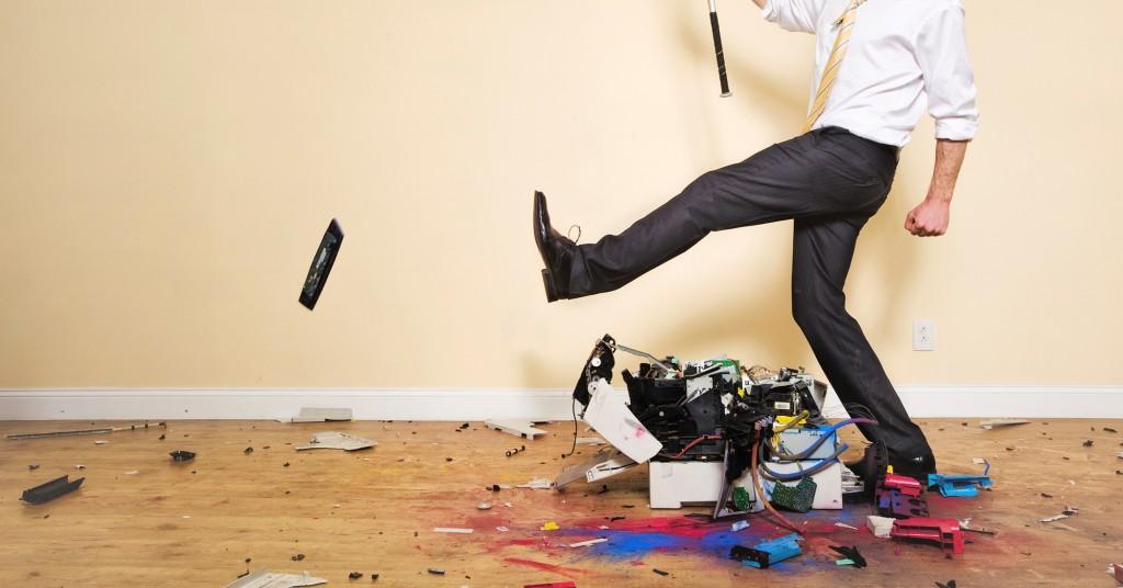 Man kicking an old broken printer