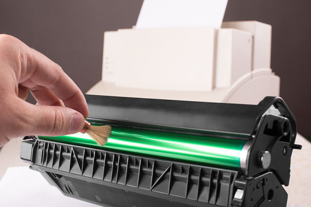 Technician hand cleaning printer toner cartridge