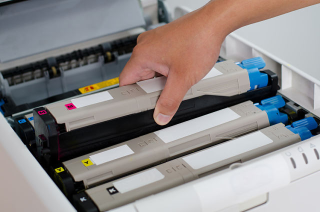 Male hand holding and puts color toner to printer.